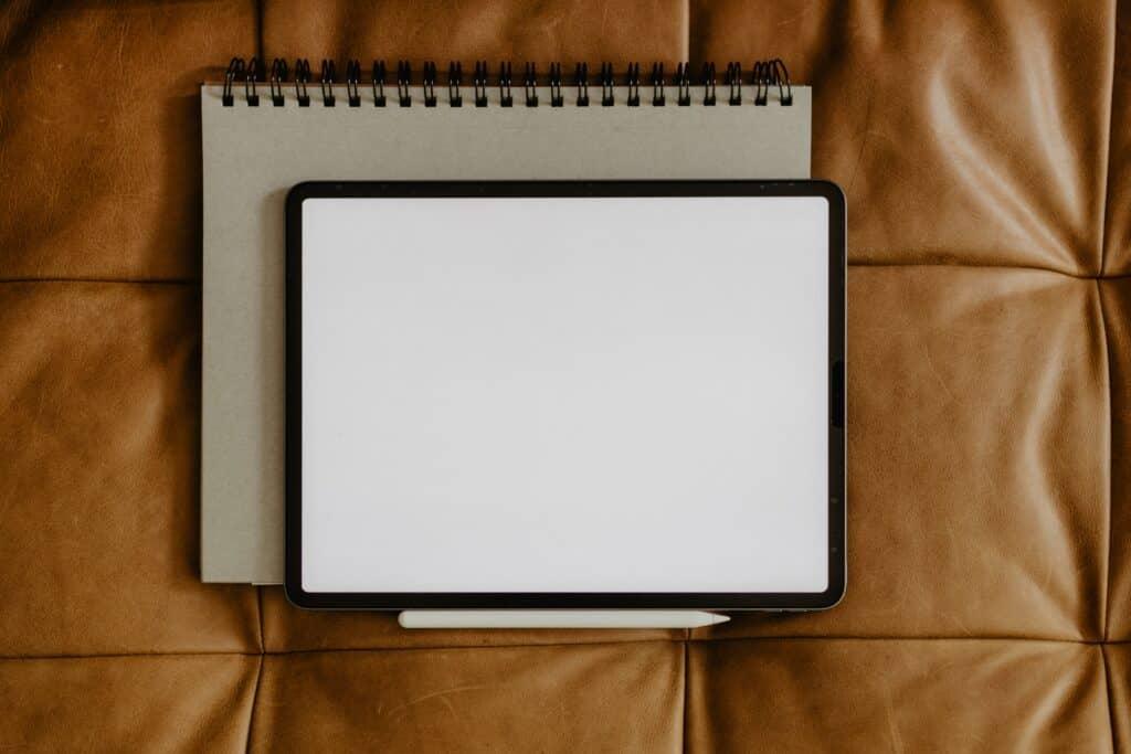 Tablet en blanco como un cuaderno en blanco con un lapiz digital debajo